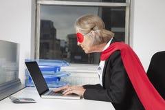 Vista lateral de la empresaria mayor en traje del super héroe usando el ordenador portátil en el escritorio de oficina Fotos de archivo