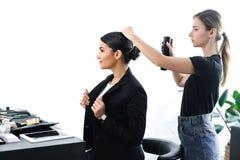 vista lateral de la empresaria que consigue el peinado fijado con la laca para el pelo imágenes de archivo libres de regalías