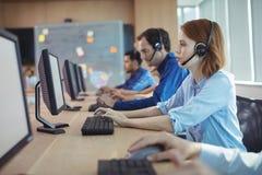 Vista lateral de la empresaria que trabaja en el centro de atención telefónica imágenes de archivo libres de regalías