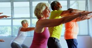 Vista lateral de la gente mayor de la raza mixta activa que ejercita en el estudio 4k de la aptitud metrajes