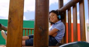 Vista lateral de la música que escucha de la colegiala de la raza mixta en los auriculares en el patio 4k de la escuela almacen de video