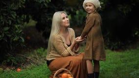 Vista lateral de la madre de amor con la niña en prado verde con la cesta de fruta en huerta soleada verde Cámara lenta completa  almacen de metraje de vídeo