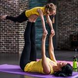 Vista lateral de la madre joven y su de la hija que hacen los ejercicios que practican la yoga junta en casa foto de archivo libre de regalías