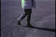 Vista lateral de la mitad inferior del cuerpo de la persona que camina en el asfalto almacen de video