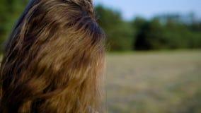 Vista lateral de la morenita joven con los pendientes que llevan del maquillaje pesado y de la mirada lejos en el fondo de la nat metrajes