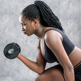 Vista lateral de la muchacha adolescente negra que se resuelve con pesa de gimnasia Fotografía de archivo libre de regalías