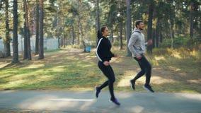 Vista lateral de la muchacha apuesta y del individuo de la gente joven que hacen deportes en el parque que corre y que salta junt almacen de video
