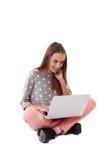 Vista lateral de la muchacha casual feliz que se sienta en el piso y que usa el la Imagenes de archivo