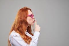 Vista lateral de la muchacha con el pelo castaño que da la muestra del silencio Imagen de archivo libre de regalías