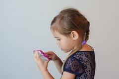Vista lateral de la muchacha de cuatro años seria que golpea ligeramente el teléfono elegante Imagen de archivo