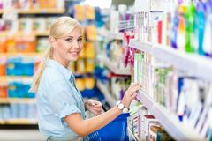 Vista lateral de la muchacha en la tienda que elige los cosméticos Fotografía de archivo