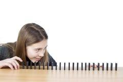 Vista lateral de la muchacha linda que mira dominós alineados en la tabla de madera aislada en el fondo blanco Imágenes de archivo libres de regalías