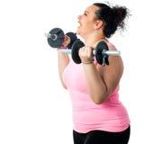 Vista lateral de la muchacha obesa que hace entrenamiento Imagen de archivo