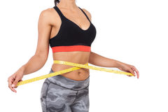Vista lateral de la muchacha que mide su cintura Fotos de archivo