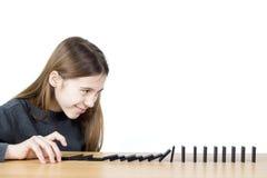 Vista lateral de la muchacha sonriente que empuja dominós en el tablero de madera aislado en el fondo blanco Foto de archivo libre de regalías