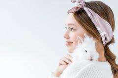 Vista lateral de la muchacha sonriente que sostiene el conejo blanco adorable Fotos de archivo