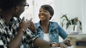 Vista lateral de la muchacha y del individuo del africam que charlan y que ríen durante la preparación a los exámenes en bibliote almacen de video