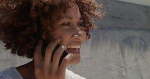 Vista lateral de la mujer afroamericana joven que habla en el teléfono móvil en la playa en la sol 4k metrajes