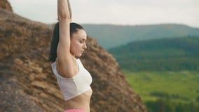 Vista lateral de la mujer atractiva del instructor de la aptitud que hace ejercicios en montañas Modelo apto del deporte del atle almacen de video