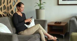 Vista lateral de la mujer caucásica que usa el teléfono móvil en el sofá en pasillo en el hospital 4k almacen de video