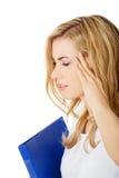 Vista lateral de la mujer con el dolor de cabeza que lleva a cabo una carpeta Fotografía de archivo libre de regalías