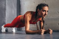 Vista lateral de la mujer del ajuste que hace ejercicio de la base del tablón foto de archivo