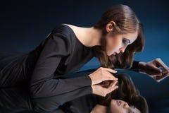 Vista lateral de la mujer del attracitve con el maquillaje que mira su reflexión foto de archivo