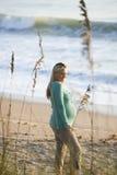 Vista lateral de la mujer embarazada que se coloca en la playa fotografía de archivo libre de regalías