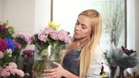 Vista lateral de la mujer en el delantal que trabaja en tienda floral y que arregla las macetas en estantes Ella siente un olor p almacen de metraje de vídeo