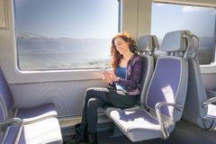 Vista lateral de la mujer en smartphone conmovedor del tren Imagenes de archivo