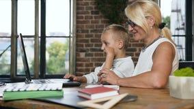 Vista lateral de la mujer envejecida media caucásica con poco nieto que se sienta en la tabla en decir acogedor del sitio de la o almacen de video