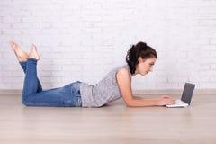 Vista lateral de la mujer hermosa que miente en el piso con el ordenador portátil Imagenes de archivo