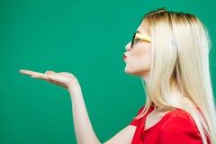 Vista lateral de la mujer joven con el pelo rubio largo, las lentes y el top rojo llevando a cabo el espacio vacío en su mano y b Imagen de archivo libre de regalías
