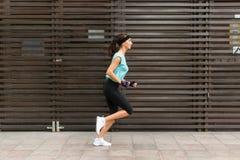 Vista lateral de la mujer joven deportiva que corre en una acera imagenes de archivo
