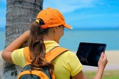 Vista lateral de la mujer joven en casquillo en el al aire libre con los comp de la tableta Imagenes de archivo
