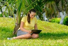 Vista lateral de la mujer joven en el césped con su tableta Imagen de archivo libre de regalías