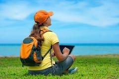 Vista lateral de la mujer joven en el césped con su tableta Fotografía de archivo libre de regalías