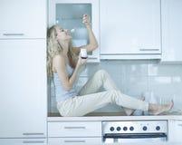 Vista lateral de la mujer joven que come el yogur mientras que se sienta en la encimera Foto de archivo