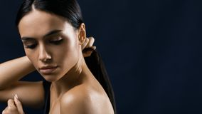 Vista lateral de la mujer joven que se sostiene el pelo negro Foto de archivo libre de regalías