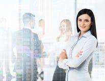 Vista lateral de la mujer morena sonriente con las manos cruzadas Figuras de los profesionales jovenes en ropa formal en el backg Foto de archivo libre de regalías