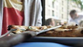 Vista lateral de la mujer que come la pizza en restaurante auténtico italiano almacen de metraje de vídeo
