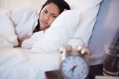 Vista lateral de la mujer que es despertada por el reloj de alarma Fotografía de archivo libre de regalías