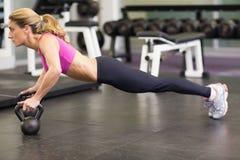 Vista lateral de la mujer que hace pectorales con las campanas de la caldera en gimnasio Fotografía de archivo