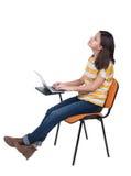 Vista lateral de la mujer que se sienta en una silla para estudiar con un ordenador portátil Foto de archivo