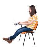 Vista lateral de la mujer que se sienta en una silla para estudiar con un ordenador portátil Fotografía de archivo libre de regalías