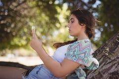 Vista lateral de la mujer que usa el teléfono elegante Imagen de archivo