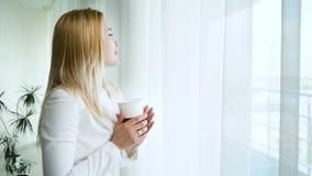 Vista lateral de la mujer rubia hermosa que mira hacia fuera la ventana y que bebe el café metrajes