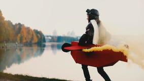 Vista lateral de la niña feliz que corre a lo largo de paisaje del lago de la ciudad de la puesta del sol en traje plano de la d metrajes