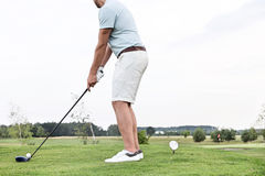 Vista lateral de la sección baja del hombre que juega a golf contra el cielo claro foto de archivo