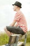 Vista lateral de la sentada adolescente en banco Fotografía de archivo libre de regalías